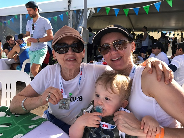 Three  generations (Mum, me and my son Riley in a pram) did the run together in 2017 – recovering at the Accenture tent.