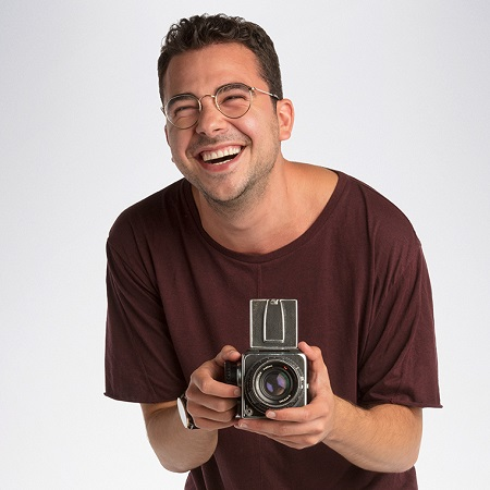 Ryan smiling while holding a video camera