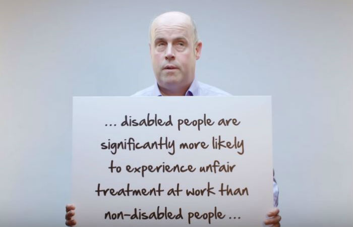 "Paul Clayton from Inclusion Starts With I video holding placard saying ""...disabled people are significantly more likely to experience unfair treatment at work than non-disabled people..."""