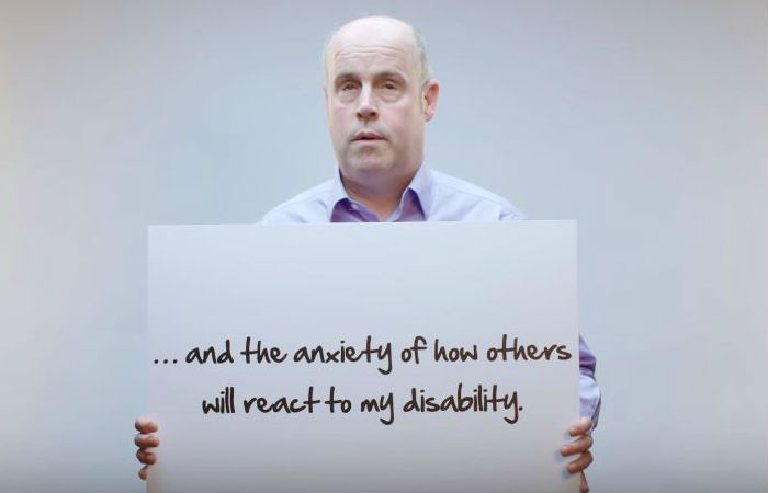 "Paul Clayton in Accenture's Inclusion Starts With I video holding placard saying ""...and the anxiety of how other will react to my disability."""