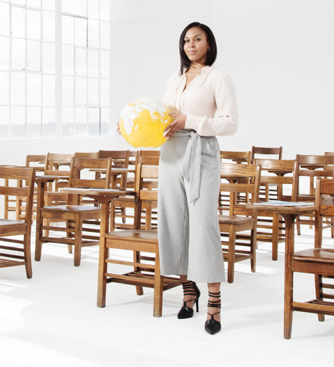 Lady standing in the middle of chairs while holding a yellow globe ball