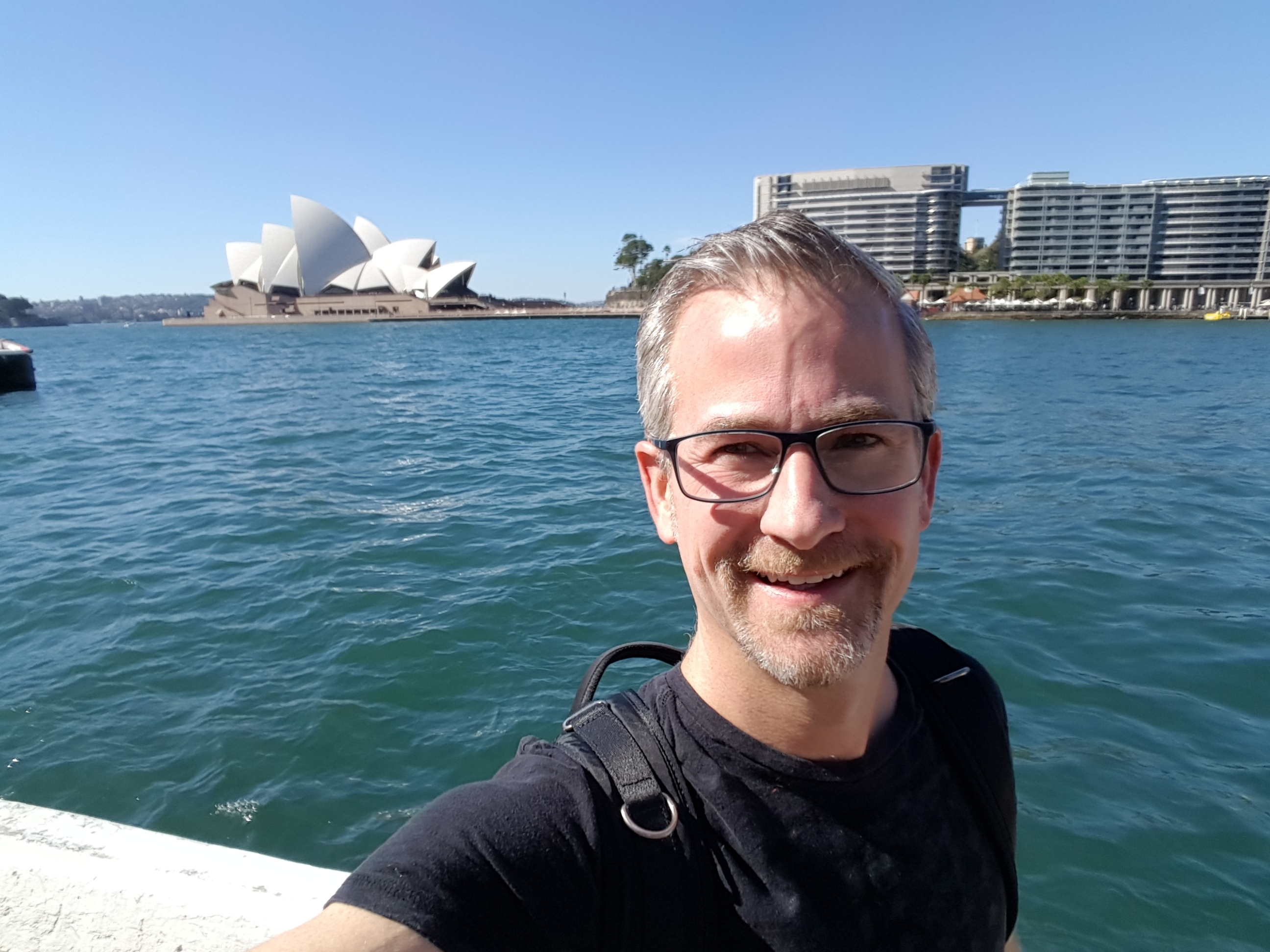 Randy posting for a picture with the Sydney Opera house on the background