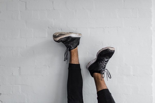 Legs and Shoes upside down against wall