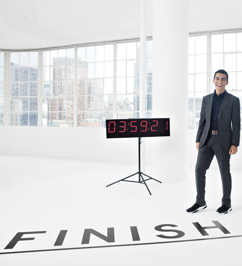 Man who's wearing a tuxedo standing beside a timer that states 3:59:21