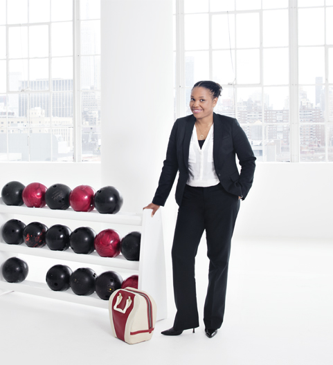 Woman in a formal attire leaning on the bowling ball rack