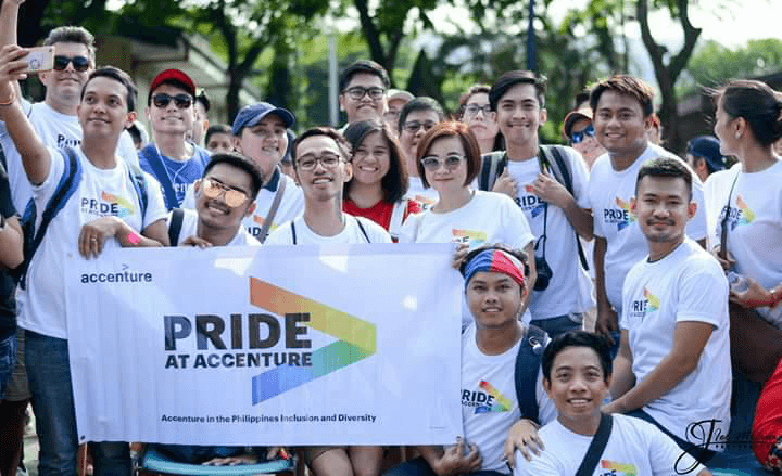 "A group of Accenture employees in the Philippines gathers with a banner that reads ""Pride at Accenture."""